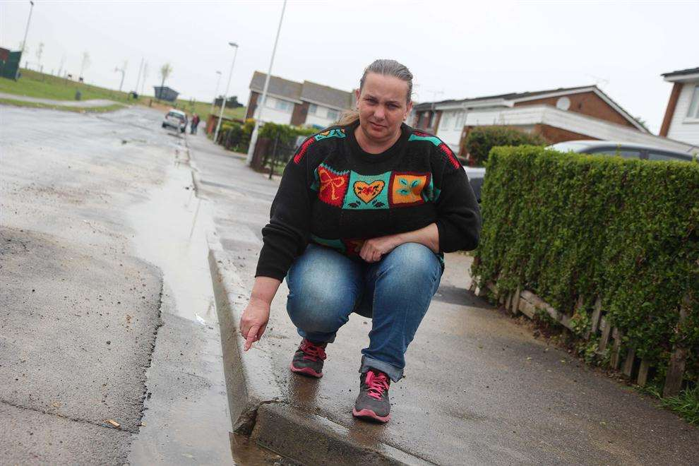 Joy Ewart next to the water leak outside her house