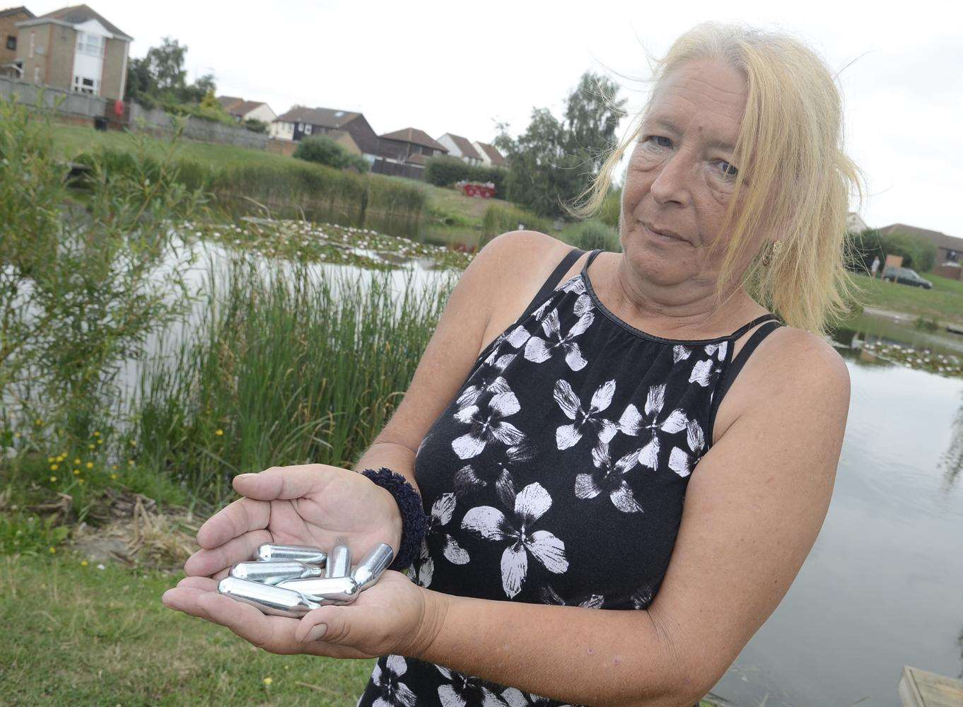 Karen Groombridge with gas gun canisters found around the lake near Newman Drive