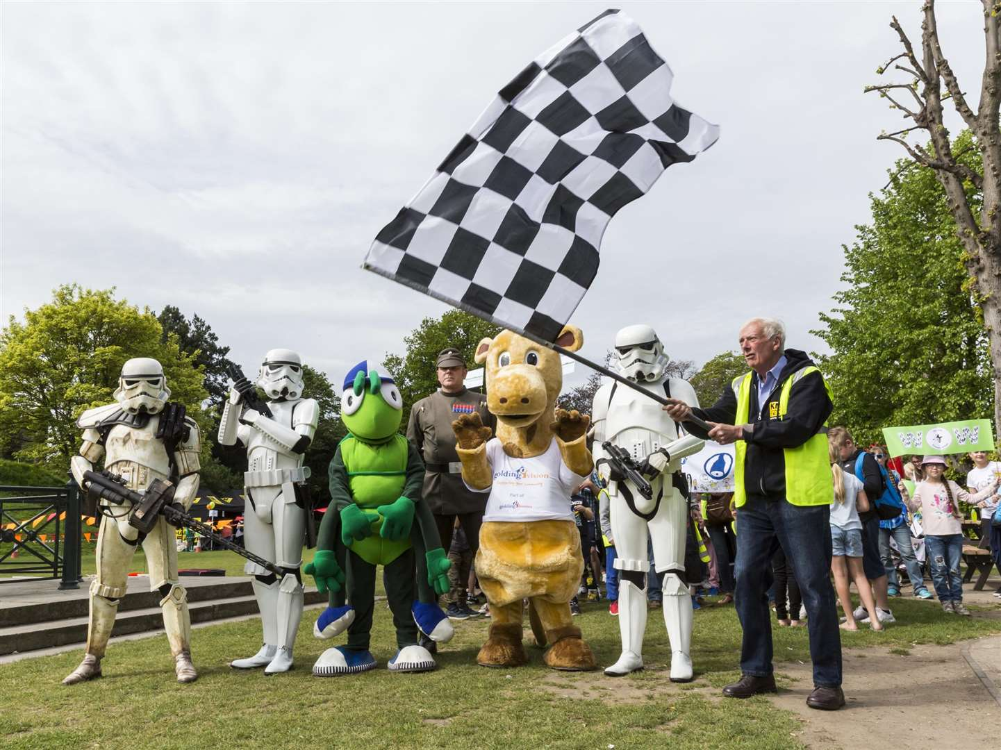 Martin Vye of the KM Charity Team waved the chequered flag while UK Garrison Stormtroopers, Buster Bug, and Gerald Giraffe headed up the record-breaking walking bus. (1969084)