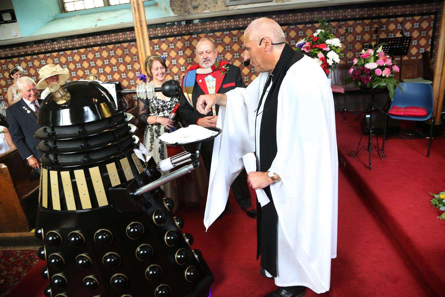 Fortunately the Dalek only interrupted the ceremony to provide the ring, handing it here to rector of St Peter & St Paul's Graham Herbert.