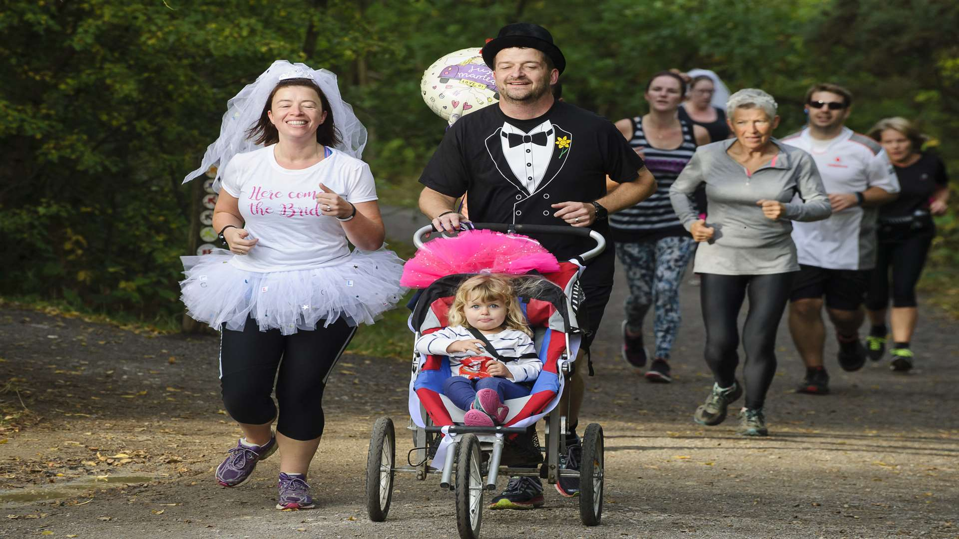 Becky and Matt run the course, with daughter Emily, 2, in the buggy. Picture: Andy Payton