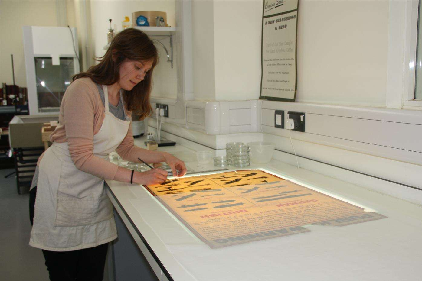 KCC conservation officer Macaulay Bristow works on restoring a poster from the First World War