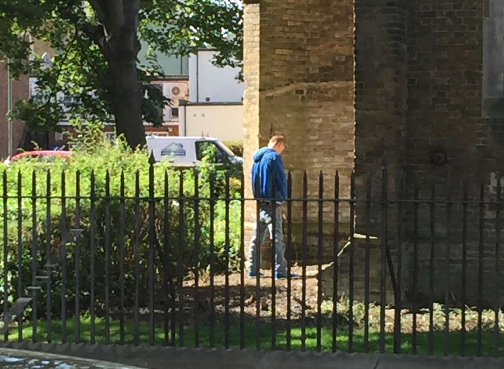 The man is snapped relieving himself against the historic building