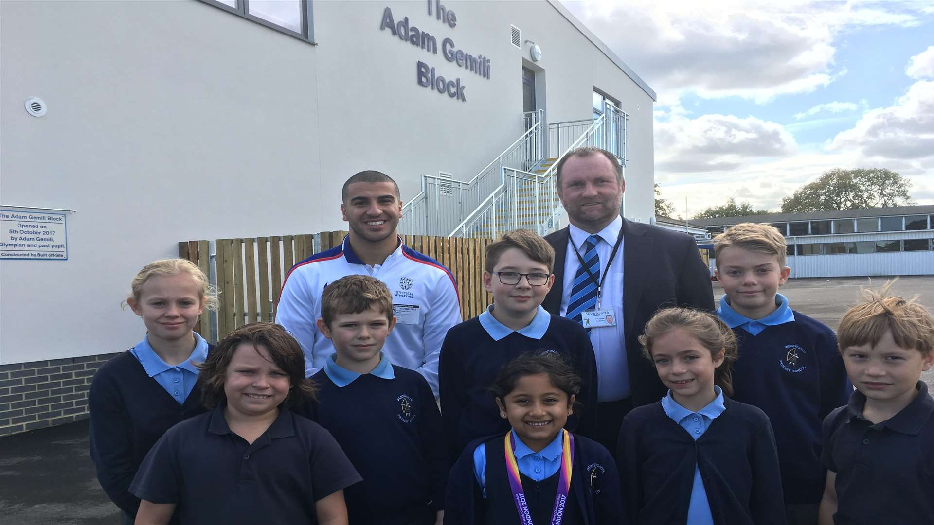Sprinter Adam Gemili is welcomed by headteacher Paul Langridge and pupils at his old school