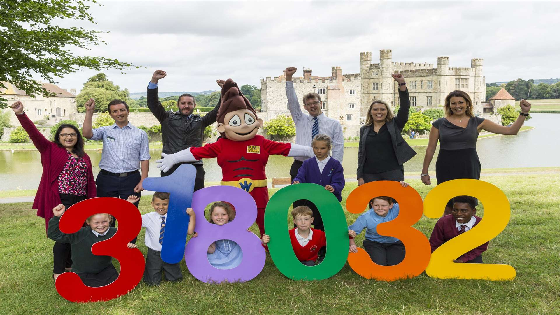 Green travel champions: pupils, supporters, and mascot Wowzer reveal the record breaking number of cars off the road at a celebration at Leeds Castle.