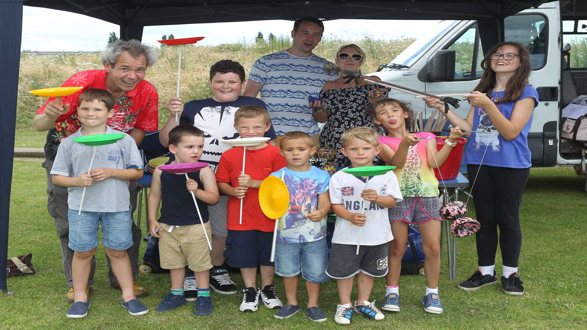 Tom from TK Arts left in red shirt with children with circus props at Milton Creek Country Park, in 2016