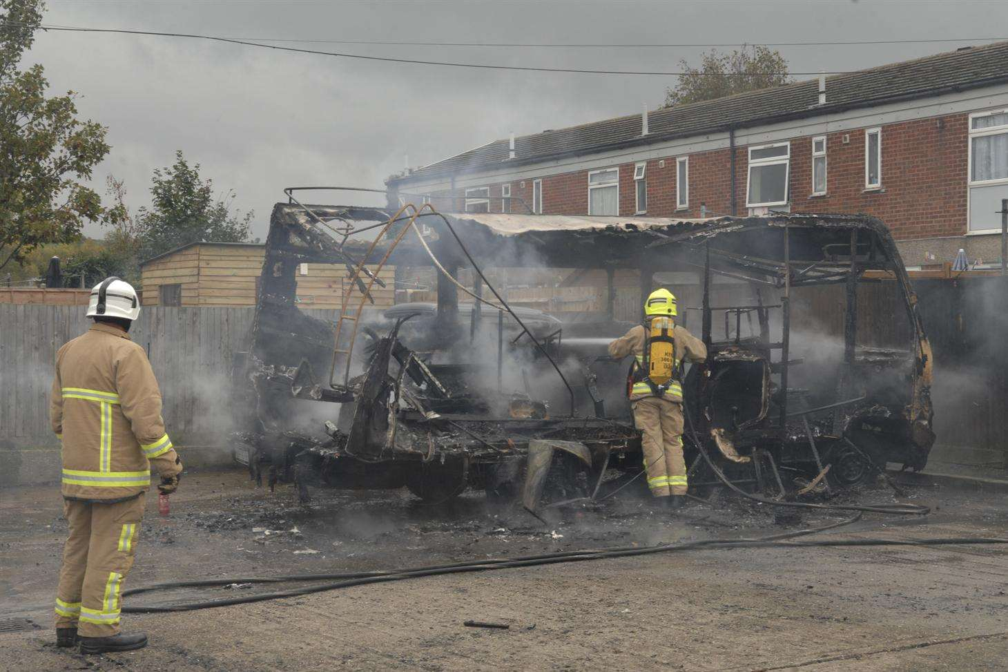 Firefighters damp down what is left of the campervan