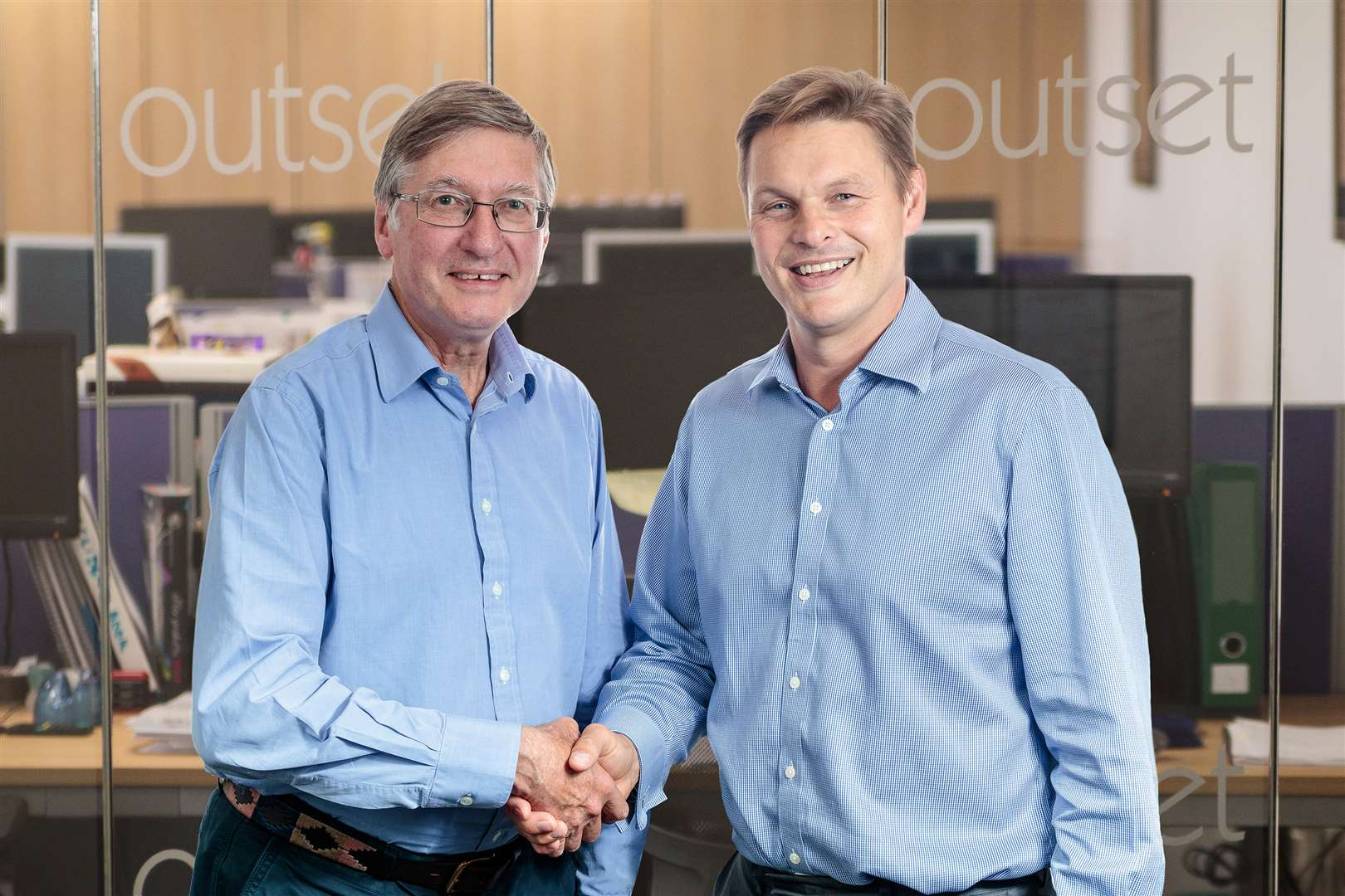 Outset Group chief executive Jonathan Gauton, right, shakes hands on the takeover with Nicholas Moore