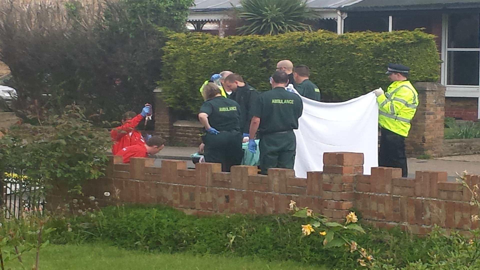 Paramedics treat the injured man behind a screen