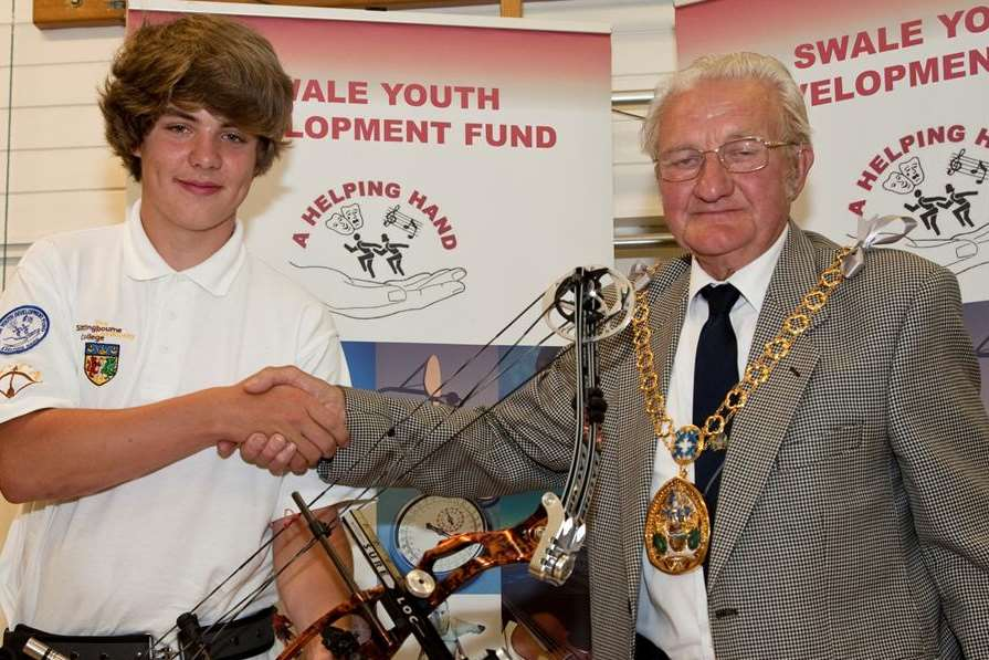 Mayor Cllr George Bobbin presents a compound bow to Charlie Collis