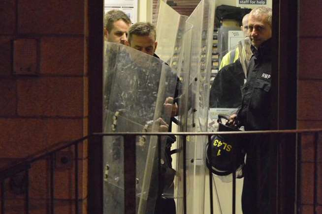 Last November's riot at HMP Maidstone. Officers in riot gear are seen leaving the building