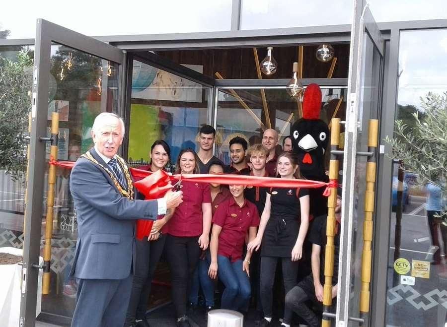 Cllr Roger Dalton, mayor of Tonbridge and Malling, cuts the ribbon of the new Nando's.