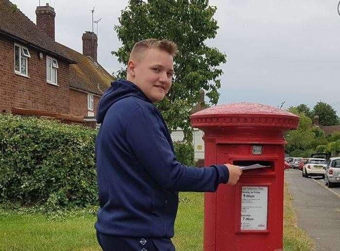 A student from The Hayesbrook School, Louis in Year 7, posting a letter to residents at Tonbridge House Care Home
