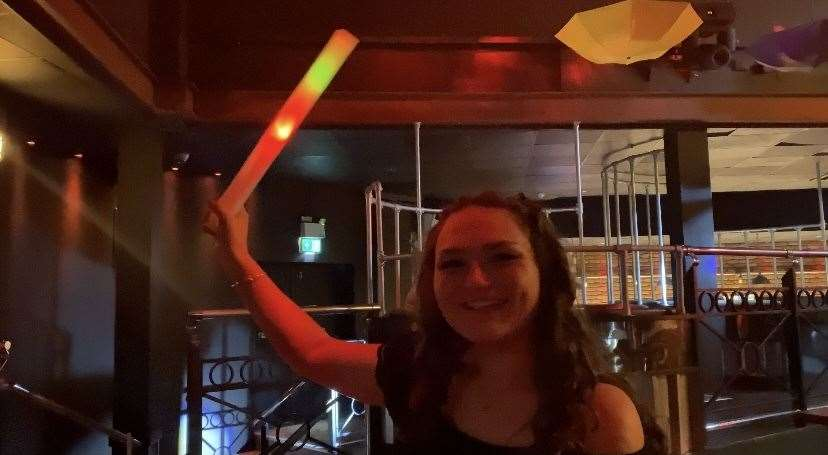 To attract the attention of the bar staff, you wave a glowing foam stick in the air