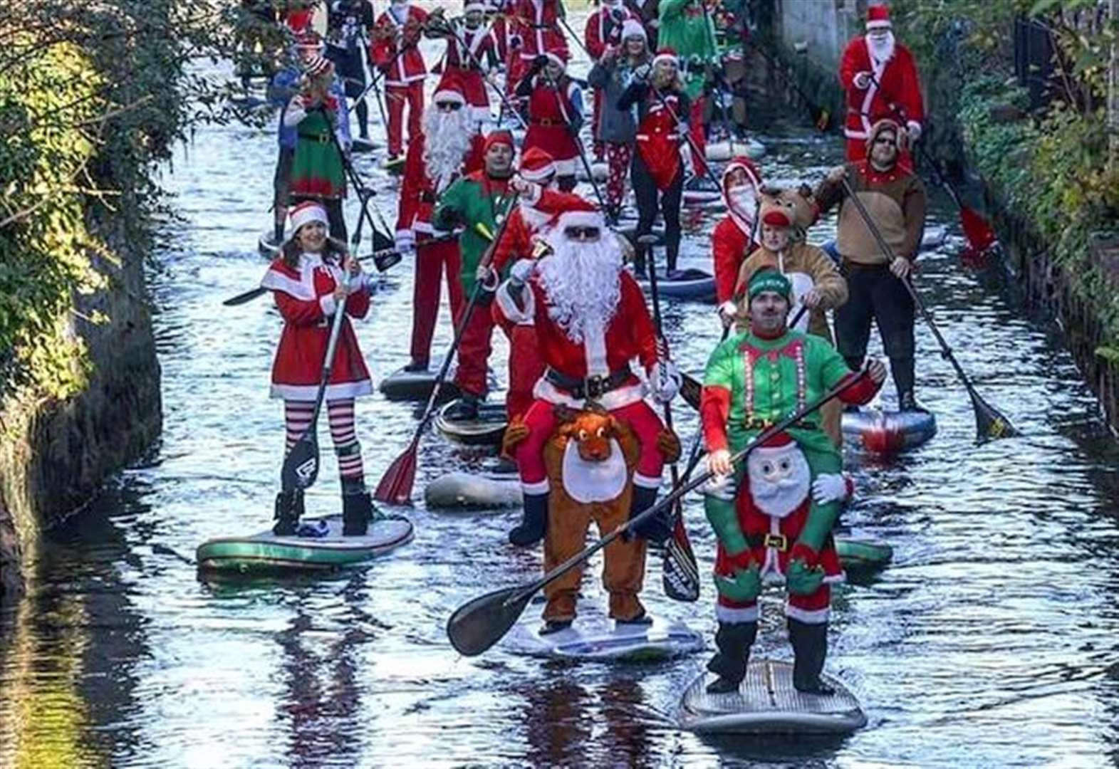 Santa paddle-board run on river
