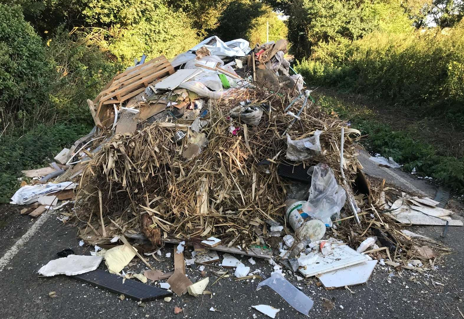 Fly-tipped rubbish mountain blocks road