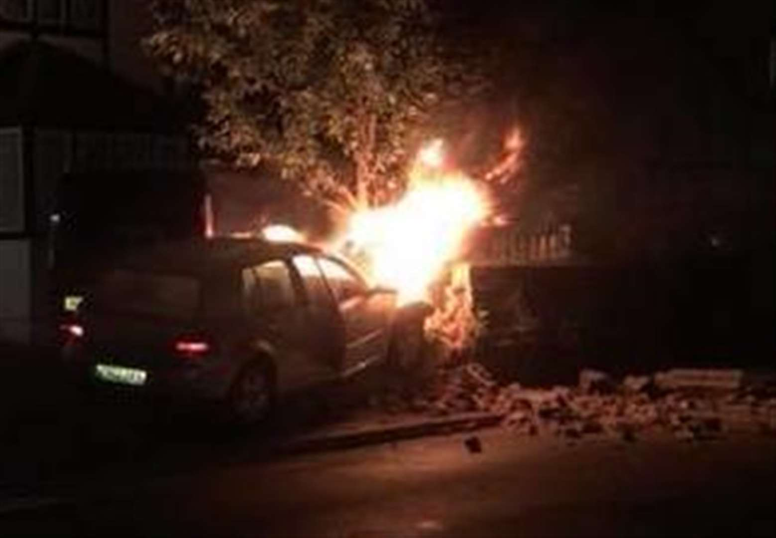 Car smashes into wall and bursts into flames