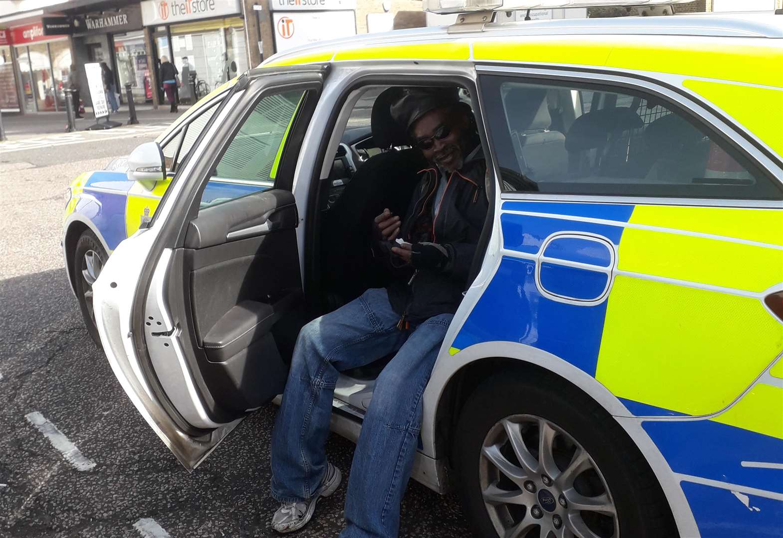 Man poses for pictures in unlocked police car