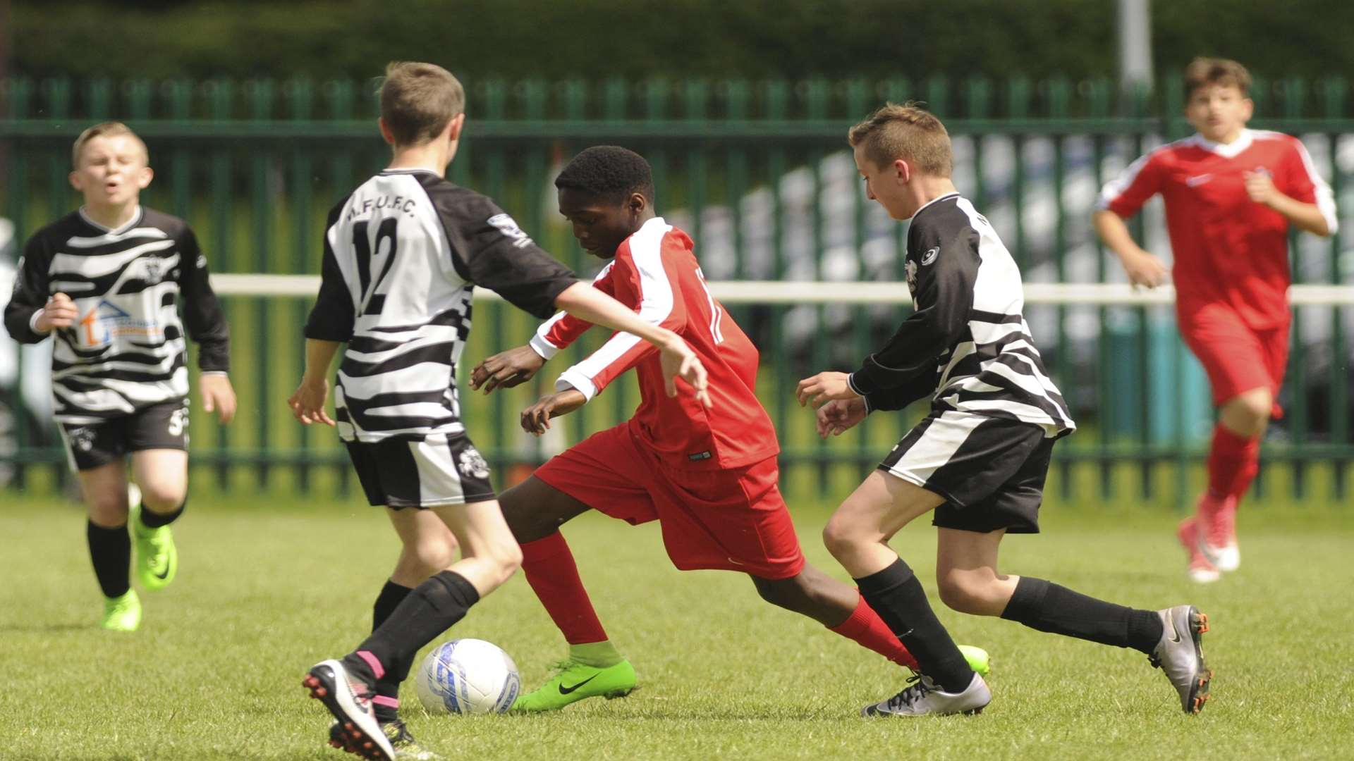 Rainham Kenilworth (red) take the game to Milton & Fulston United in the Under-13 League Cup final Picture: Steve Crispe