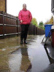 Mandy Beeton with the flooded sewerage drain outside her home in Minster