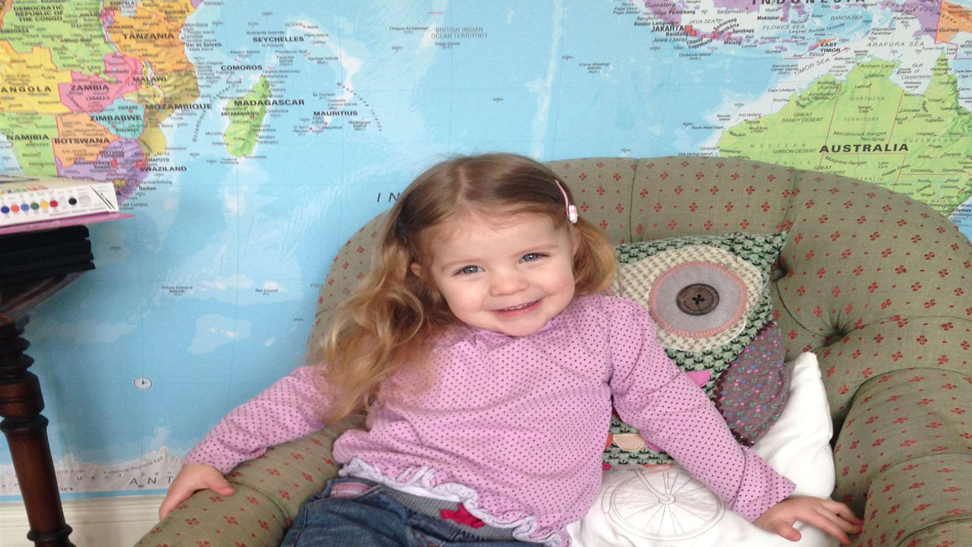 Richard's daughter Genevieve in front of their map feature wall