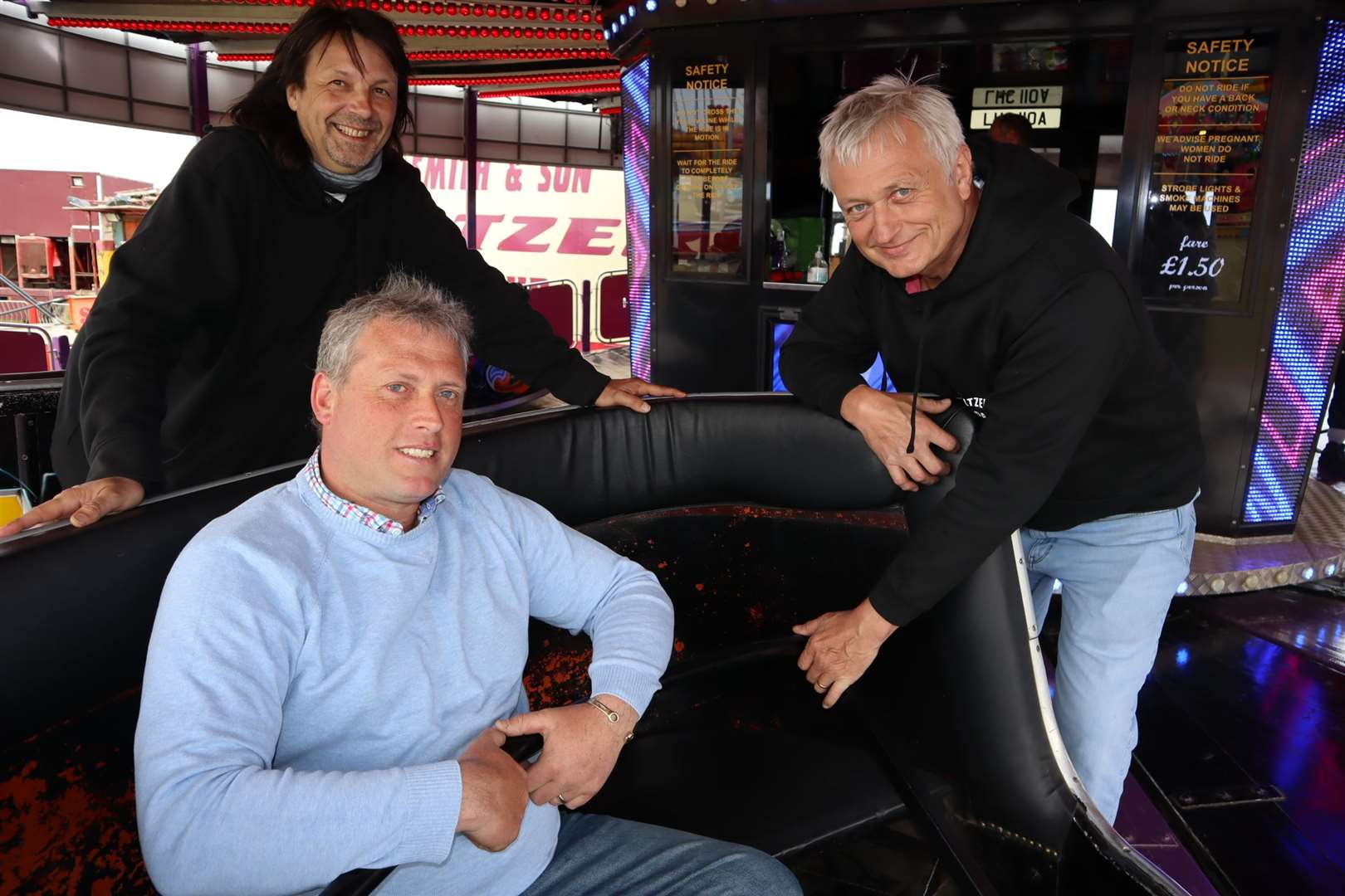 Cllrs Mike Baldock, left, and Richard Palmer give funfair boss Carlos Christian a hand on the waltzer at Smith's funfair at Barton's Point, Sheerness