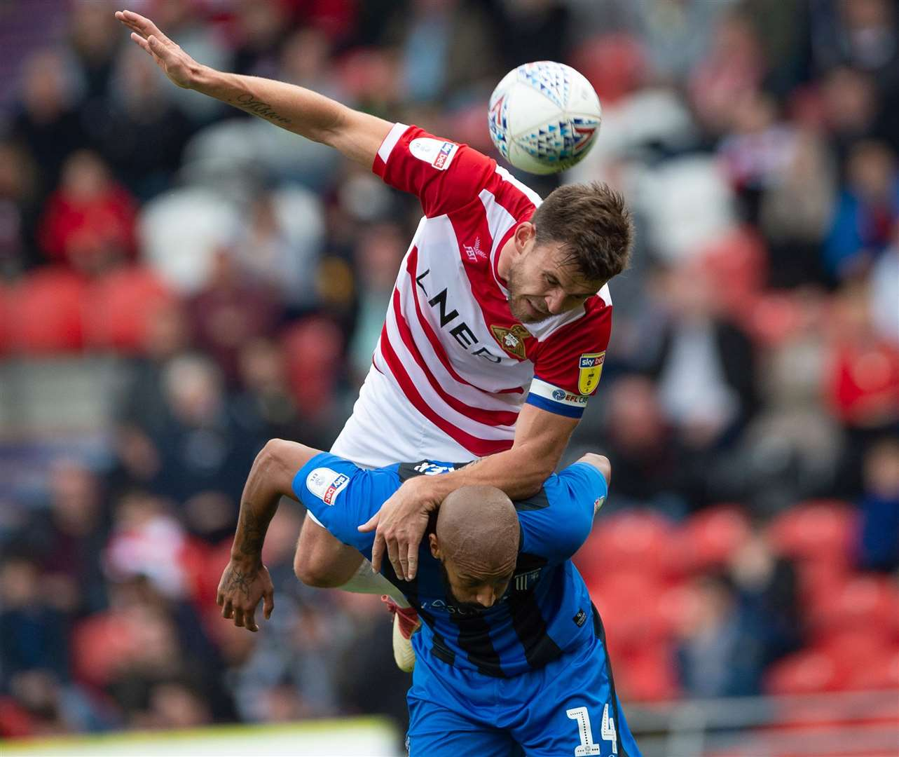Andy Butler climbs all over Gillingham's Josh Parker. Picture: Ady Kerry