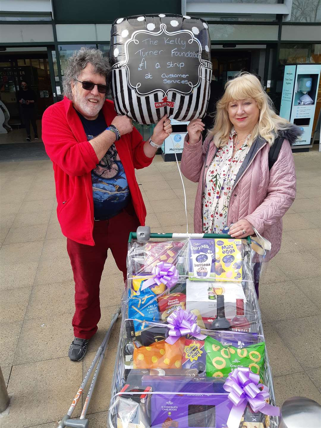 Martin and Linda Turner outside Morrisons with the trolley of goods raffled for the fundraising. Picture:Sam Lennon