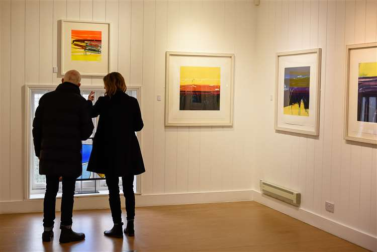 Visitors looking at the work of Barbara Rae in her latest show Images of Time Passing
