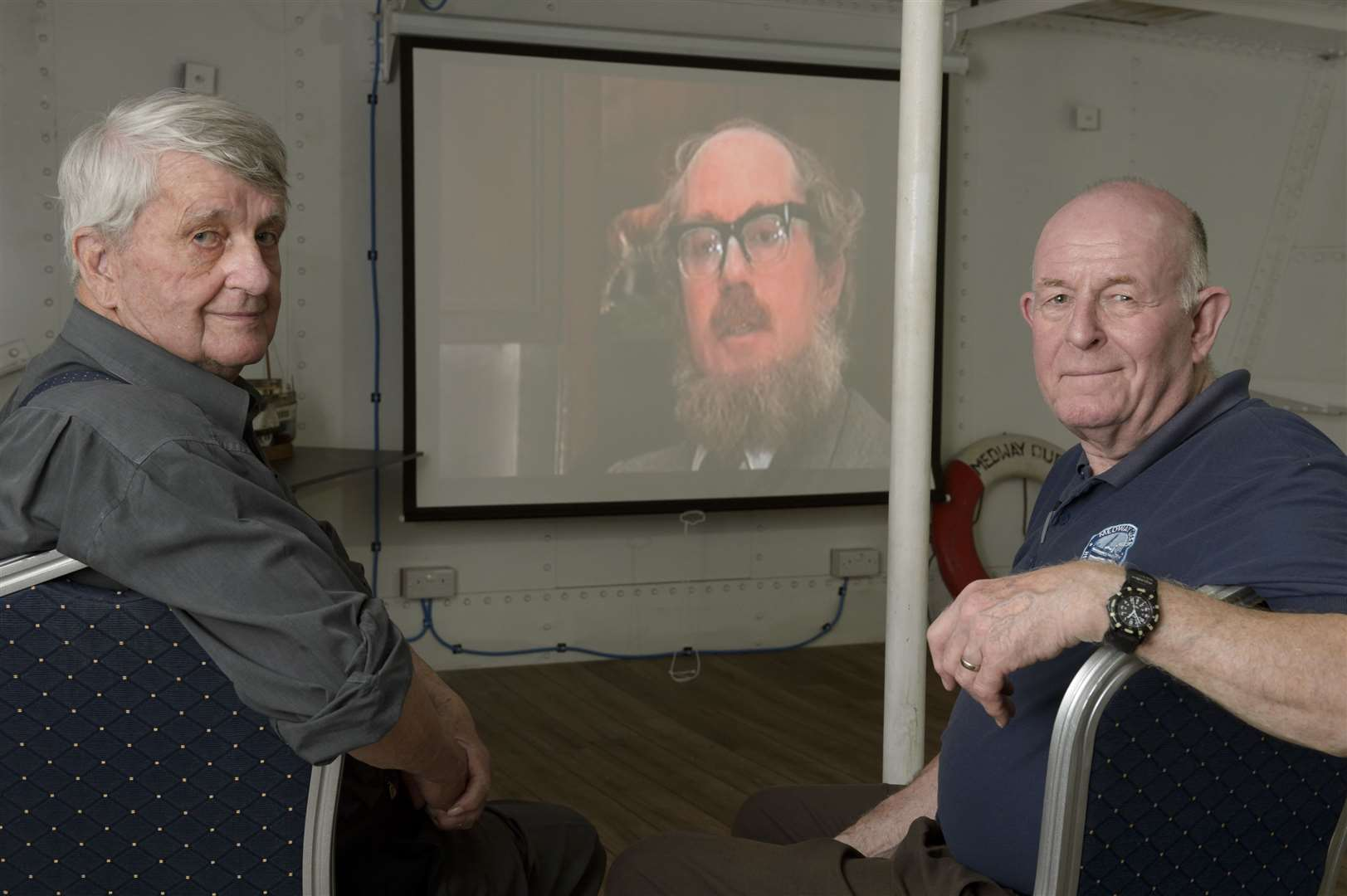 Publicity officer Brian Goodhew, left, and volunteer Mark Bathurst with a showing of old Medway Queen news footage. Regular open day for the Medway Queen paddle steamer, at Gillingham Pier, Gillingham. It's also the Dunkirk evacuation anniversary and as a veteran ship the Dunkirk pennant is being flown.Picture: Andy Payton (2333248)