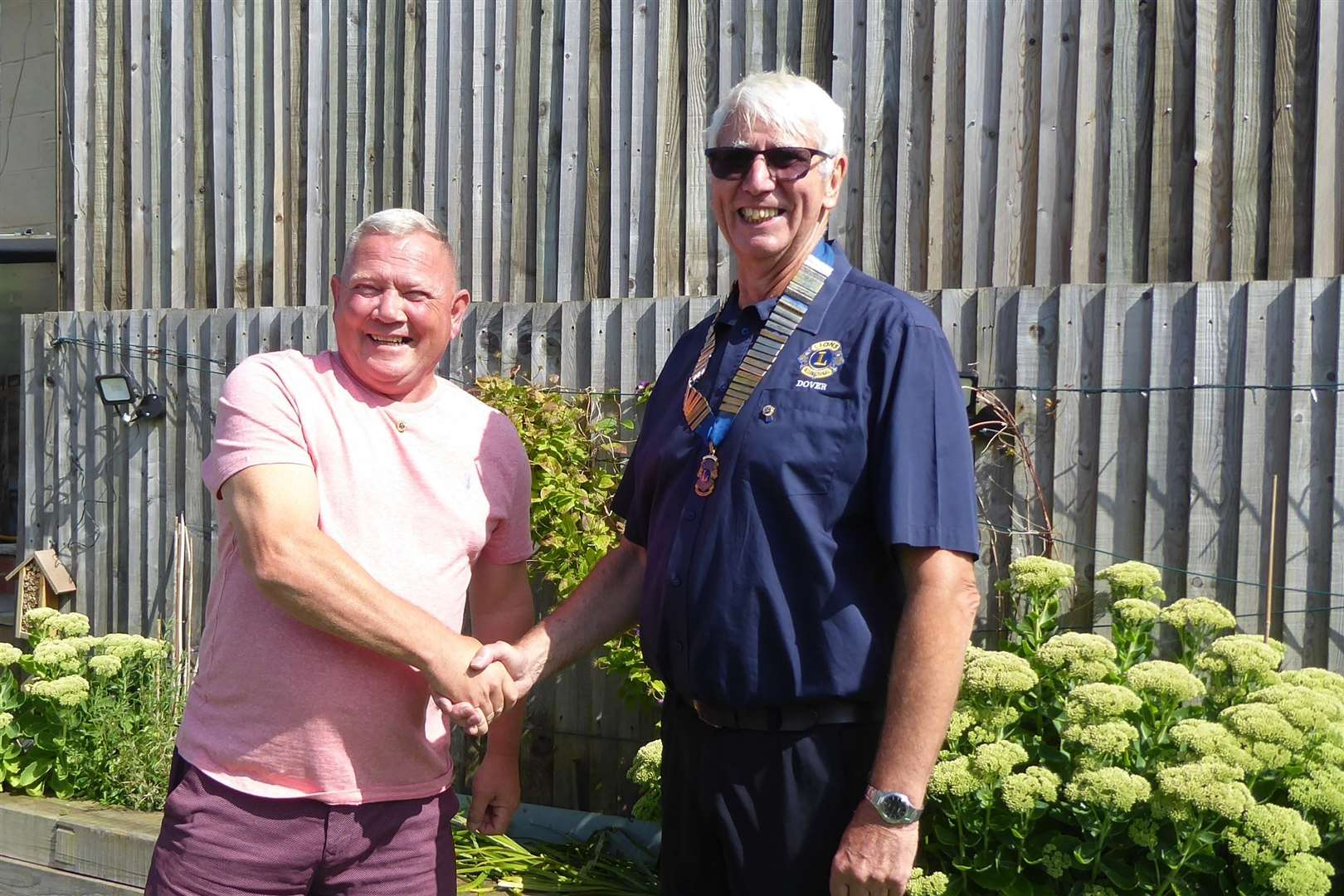 Outgoing President Garry Dixon passes the baton to Len Button.  Photo: Lions Club of Dover