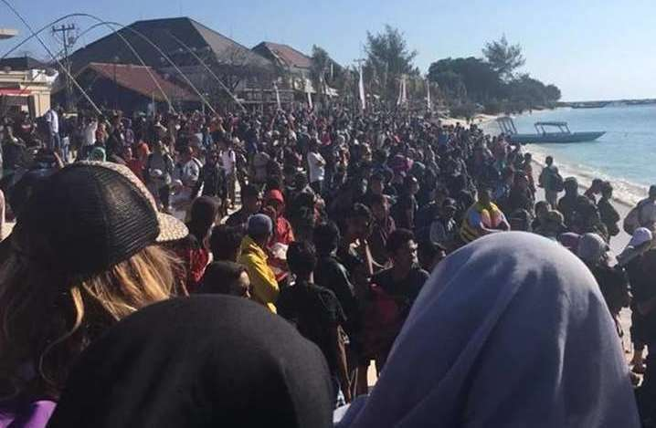 People on the beach in Lombock, Indonesia, trying to escape the island. Picture: Vicky Marchant