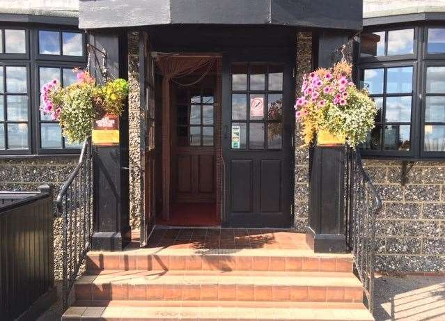 The side entrance has hanging baskets either side of the steps