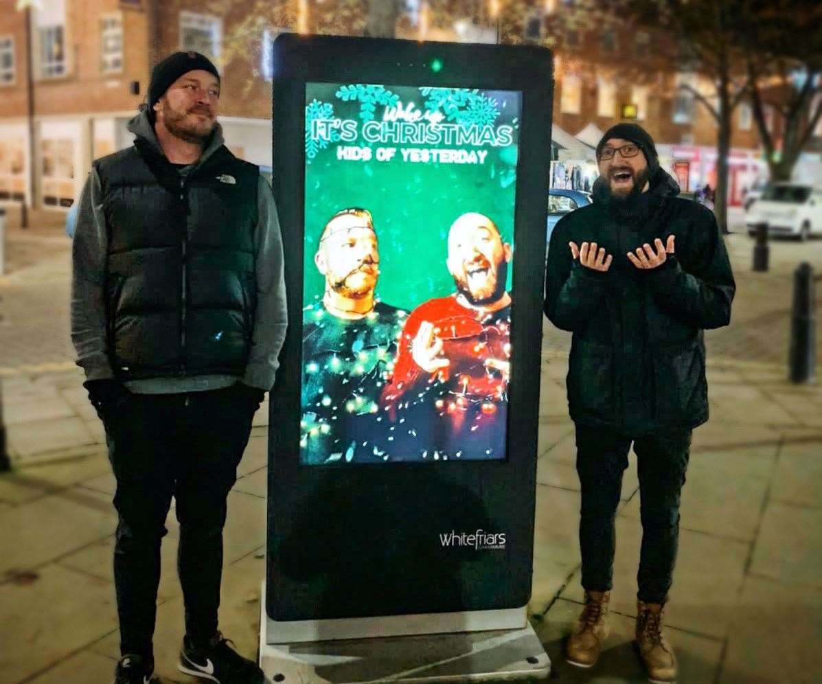 (Left to right) Musicians Stuart Weller and James O'Keeffe with an advert for their Christmas song in Canterbury city centre. Picture: Stuart Weller