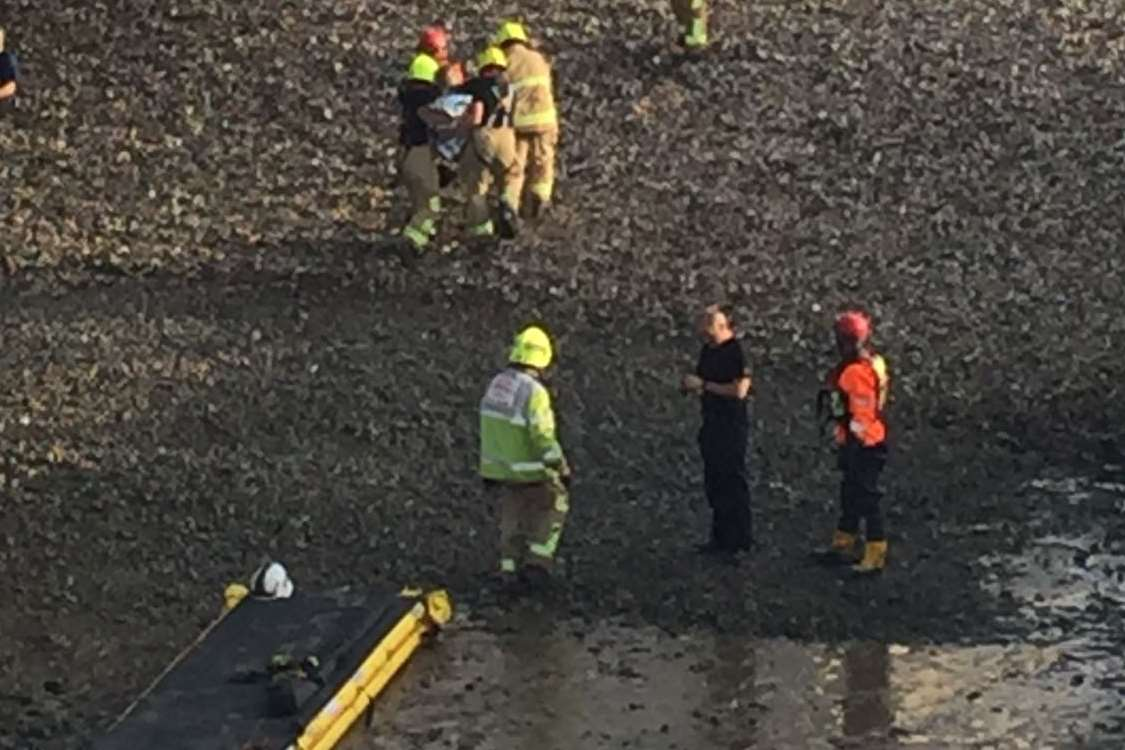 Fire crews help the woman off the beach