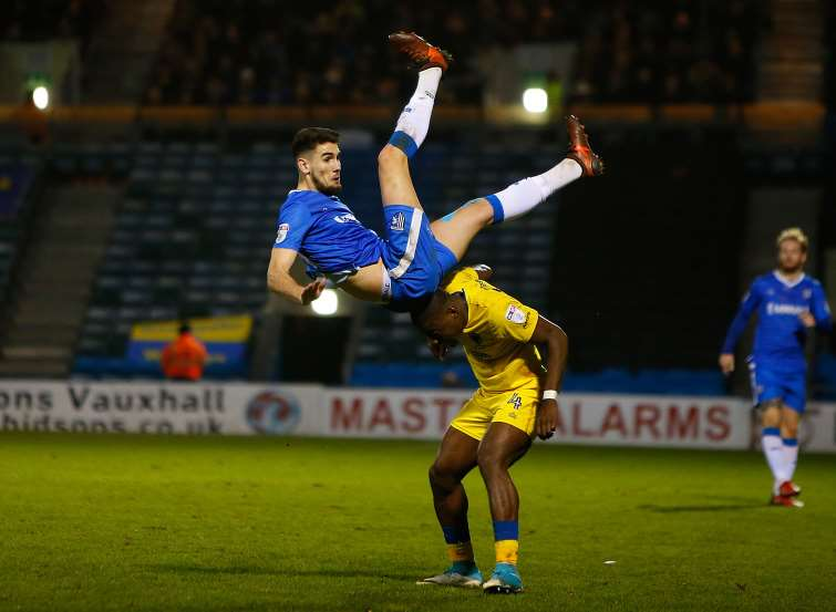 Gillingham striker Conor Wilkinson takes a tumble Picture: Andy Jones