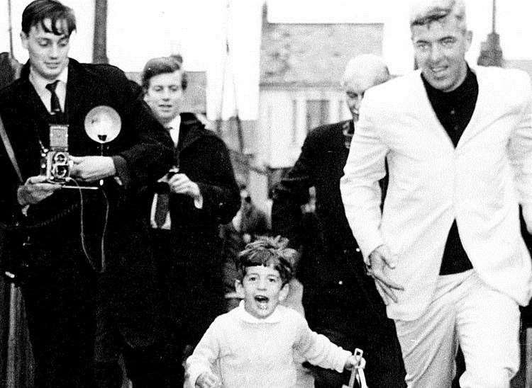 John F Kennedy Jnr races for the beach accompanied by his bodyguard and a clutch of Fleet Street photographers