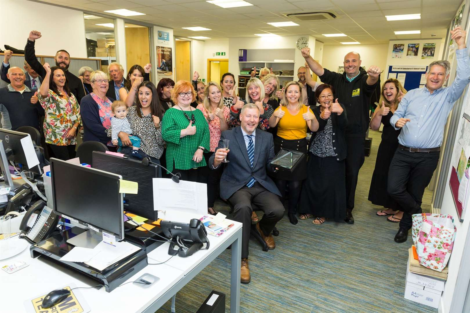 Staff and sponsors give outgoing CEO of the KM Charity Team Simon Dolby a rousing send off.