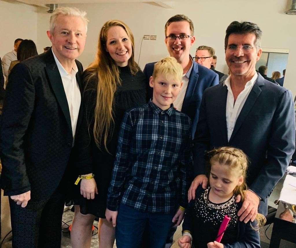 Hallie with her family, and X-Factor judges Louis Walsh and Simon Cowell. Pic: Demelza Children's Hospice
