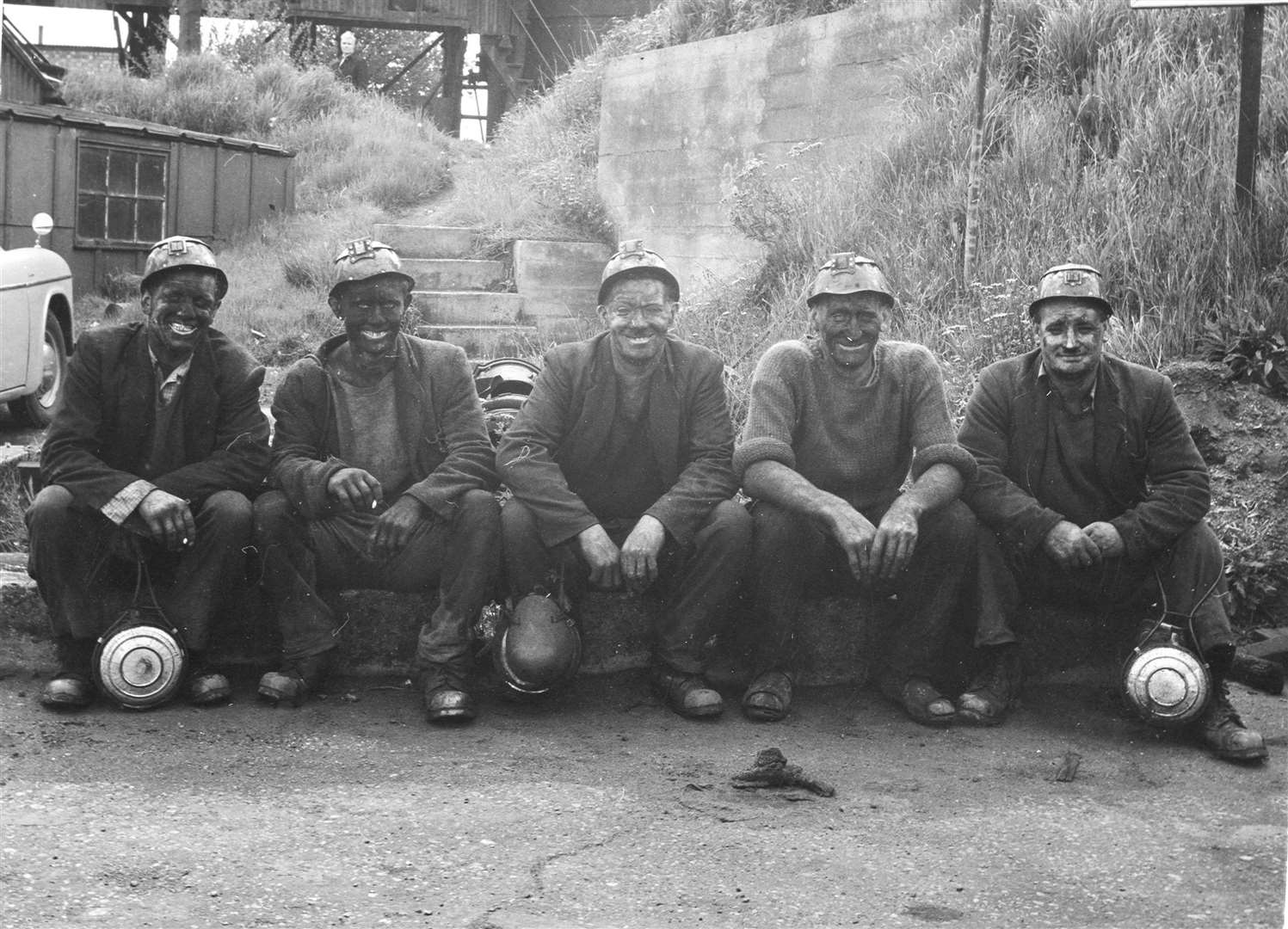 Fresh out of the pit, these bygone miners line up for a photo