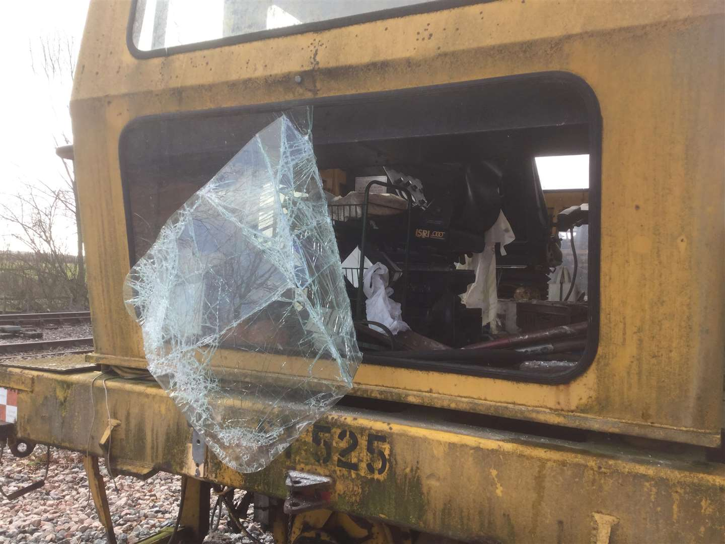Damage to the tamping machine where glass covered by plastic was smashed to gain entry to the cab above