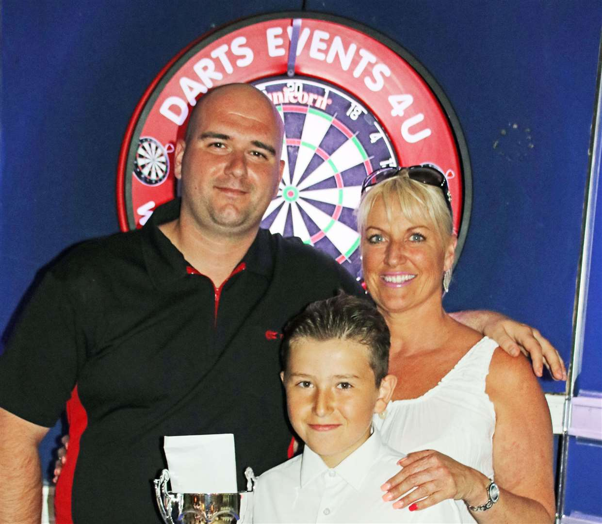 Rob Cross, left, pictured with Merlins Entertainment's Lee Dunn and her nephew Gary after winning the Sheppey Darts Classic in June 2017. Picture: Tony Cox