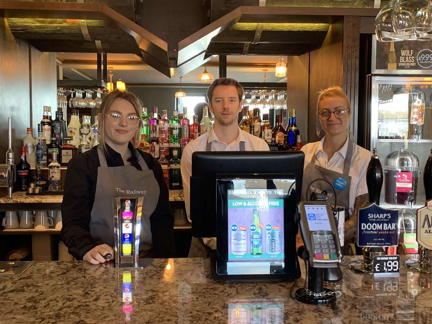 The bar staff are ready to meet their new customers at The Railway in Station Road, Rainham (18008990)