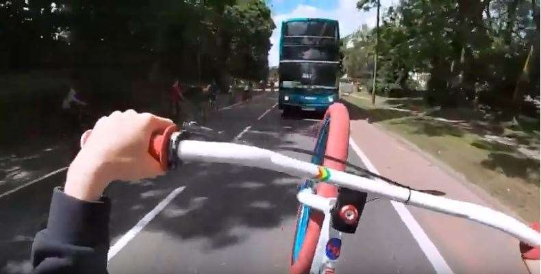 A point of view video shows one rider cycling straight towards a bus