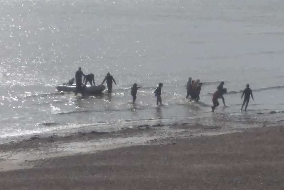 People coming ashore at Kingsdown after leaving a small boat in the water. Picture Christian Thrale