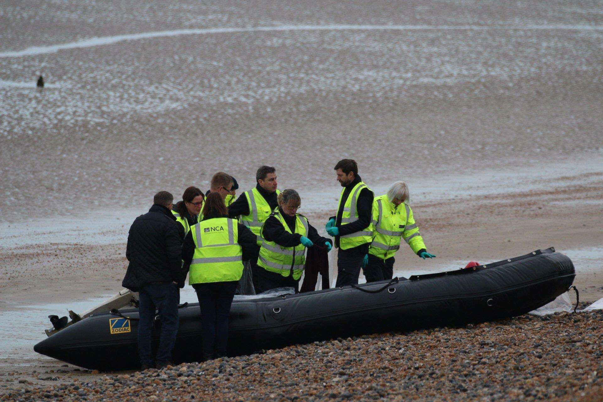 Officers wearing hi-vis National Crime Agency jackets examine a boat on the shore at Greatstone. Picture: Susan Pilcher