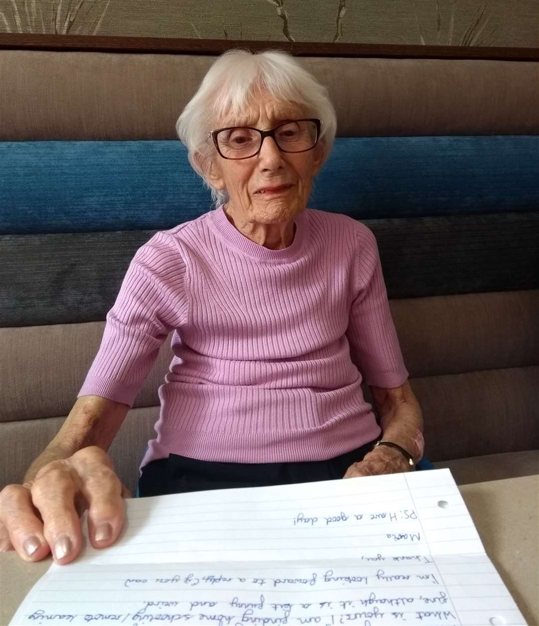 Tonbridge House Care Home resident, Jean, reading letters written by students from The Hayesbrook School