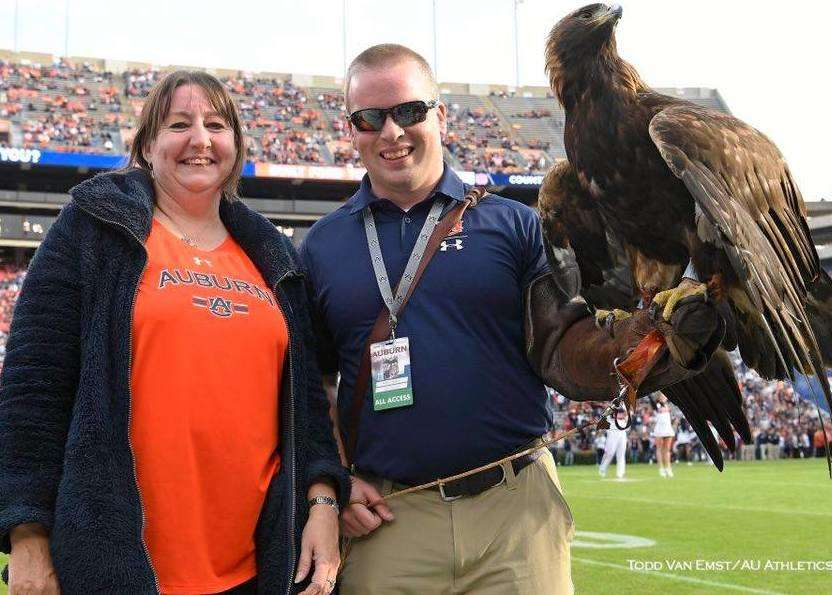 Dee Ford gets up close with the Auburn golden eagle mascot while guest of honour at an American football match