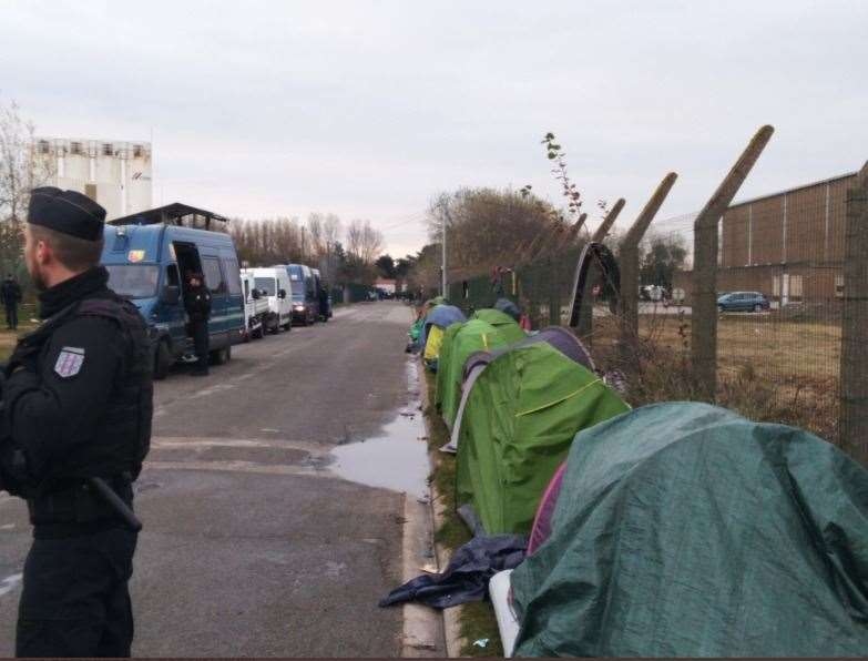French police next to tents lining the road in Calais. Picture: Poppy Cleary