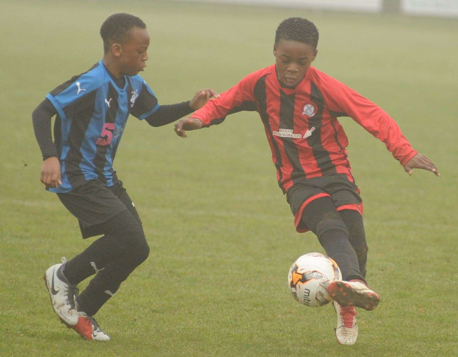 Meopham Colts Red and Omega 92 (blue/black) gets stuck in during the Under-11 Trophy Event final Picture: Steve Crispe